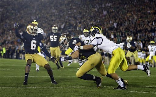 Notre Dame's Nicky Baratti is tackled by Michigan's Drew Dileo after Baratti after intercepting a pass intended for Dileo during the first half of an NCAA college football game Saturday, Sept. 22, 2012, in South Bend, Ind. (AP Photo/Darron Cummings)