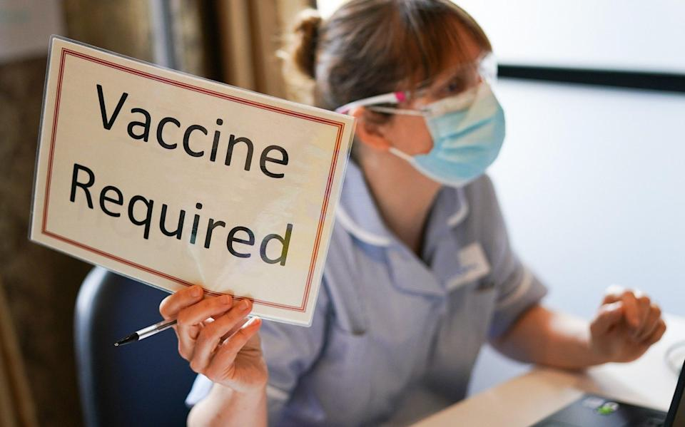 A member of the medical staff holds a sign indicating she has briefed a patient and is ready for a vaccine to be administered - Ian Forsyth /Getty Images Europe