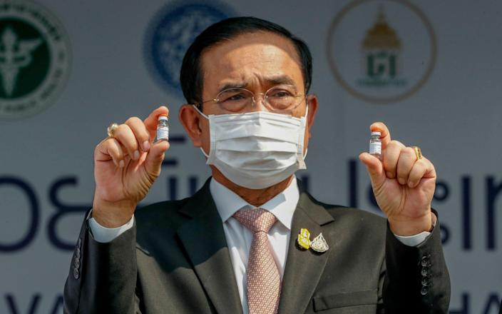 Prime Minister Prayuth Chan-ocha holds samples of the Sinovac vaccine during a ceremony to mark the arrival of 200,000 doses in a shipment at the Suvarnabhumi airport in Bangkok. Prayuth on Wednesday, June 16, 2021, declared that the country is planning to fully reopen to foreign visitors without restrictions by mid-October, as the government seeks to restart the crucial tourist industry, - AP
