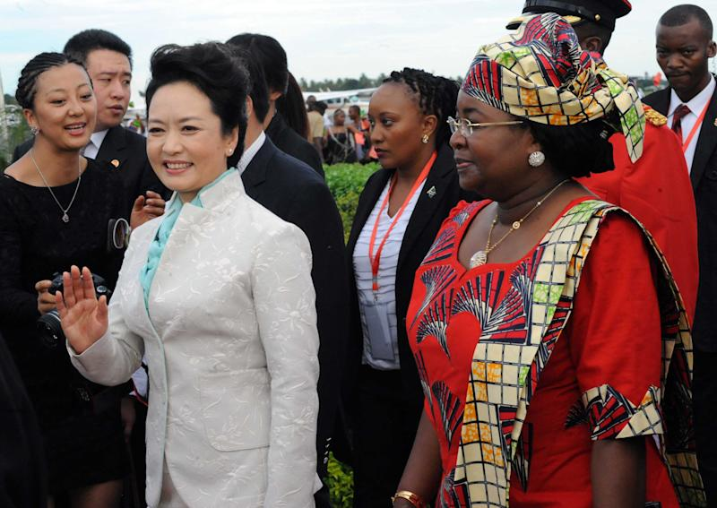 Chinese First Lady, Madame Peng Liyuan, left,, waves as she is  accompanied by Tanzanian First Lady, Salma Kikwete, right, at Julius Nyerere International Airport in Dar es Salaam, Sunday March 24, 2013. Liyuan is accompanying her husband, Chinese President in his first African tour since he became president of the second largest economy in the world. (AP Photo/ Khalfan Said)