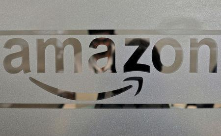 FILE PHOTO: Employees of Amazon India are seen behind a glass bearing the company's logo inside its office in Bengaluru