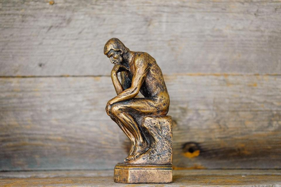 """a miniature version of Rodin's """"The Thinker"""" sculpture"""