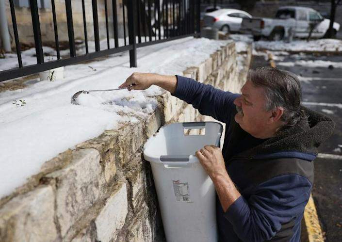 AUSTIN, TEXAS - FEBRUARY 19: Mark Maybou scraps snow into a bucket to melt it into water on February 19, 2021 in Austin, Texas. Mr. Maybou was using the water to flush his toilets since his home has no running water. Winter storm Uri brought historic cold weather causing people to lose their water as pipes broke throughout the area. (Photo by Joe Raedle/Getty Images)