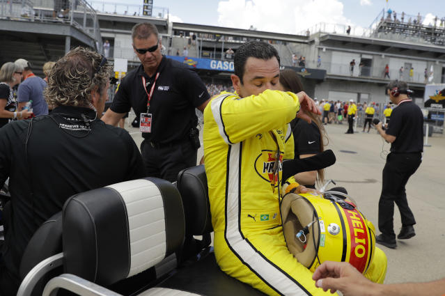 Helio Castroneves, of Brazil, wipes his face after dropping out of the Indianapolis 500 auto race after a crash at Indianapolis Motor Speedway in Indianapolis, Sunday, May 27, 2018. (AP Photo/Darron Cummings)