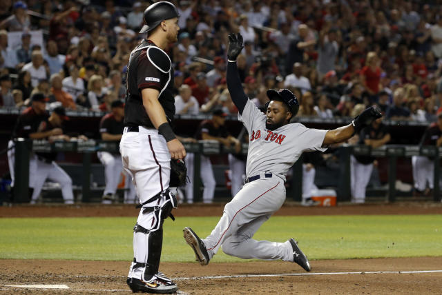 Boston Red Sox 's Jackie Bradley Jr.,right, slides to score a run in the seventh inning during a baseball game against the Arizona Diamondbacks, Saturday, April 6, 2019, in Phoenix. (AP Photo/Rick Scuteri)