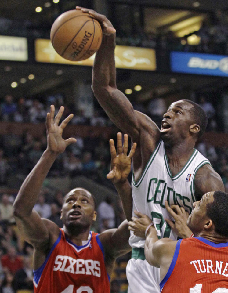Boston Celtics' Brandon Bass, center, reaches for a rebound against Philadelphia 76ers defenders Elton Brand, left, and Evan Turner during the first quarter of Game 5 in their NBA basketball Eastern Conference semifinal playoff series in Boston, Monday, May 21, 2012. (AP Photo/Charles Krupa)
