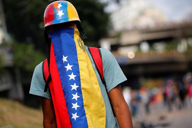 <p>An opposition supporter looks on during a blockade in an avenue while rallying against President Nicolas Maduro in Caracas, Venezuela, May 15, 2017. (Carlos Garcia Rawlins/Reuters) </p>