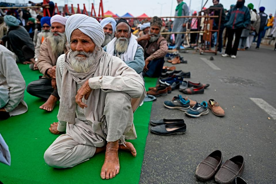 <p>Farmers sit along a blocked highway as they continue to protest against the central government's recent agricultural reforms at the Delhi-Uttar Pradesh state border in Ghazipur on 18 January 2021</p> (AFP via Getty Images)