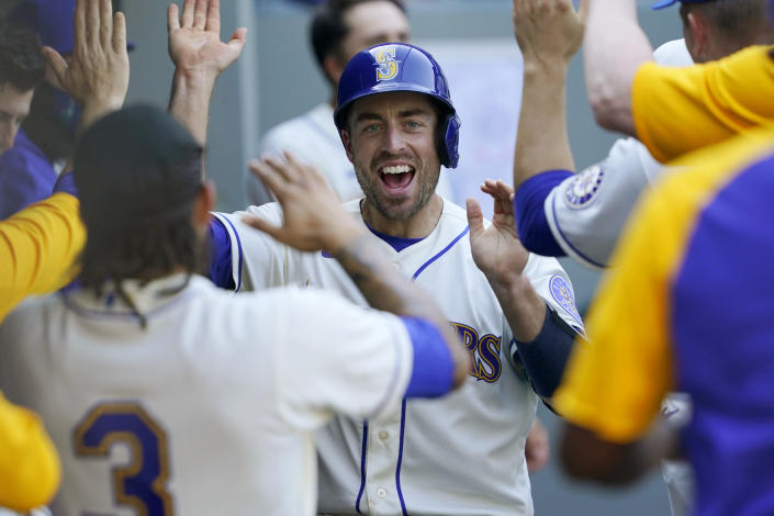 Seattle Mariners' Tom Murphy reacts in the dugout after he scored on an RBI-double hit by Mitch Haniger during the seventh inning of a baseball game against the Houston Astros, Sunday, April 18, 2021, in Seattle. (AP Photo/Ted S. Warren)