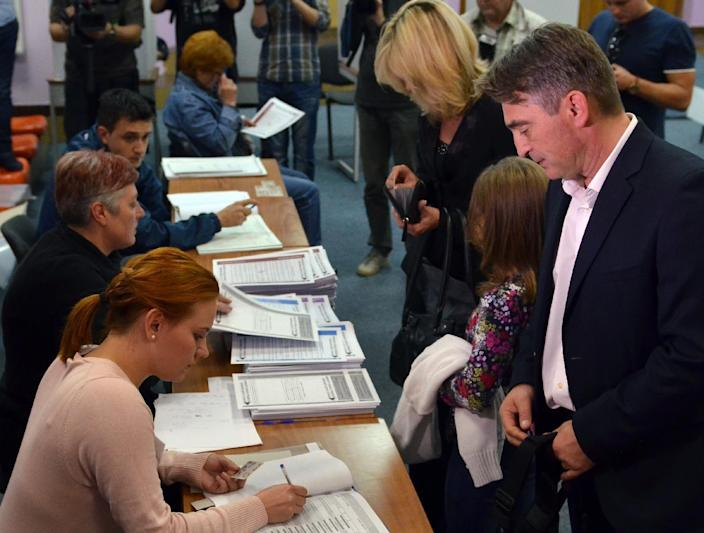 Zeljko Komsic (R), a member of Bosnia's tripartite Presidency and candidate for next term, is seen while being identified before voting at a polling stations in Sarajevo on October 12, 2014 (AFP Photo/Elvis Barukcic)