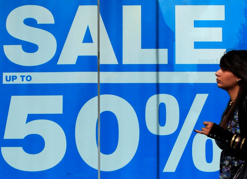 A shopper passes an advertisement on a shop in Oxford Street in London