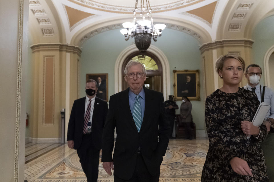 Senate Minority Leader Mitch McConnell of Kentucky, center, leaves the Senate floor, on Capitol Hill, Thursday, October 7, 2021, in Washington.  The Senate averted a US debt catastrophe by approving legislation to raise the federal limit on new borrowing by nearly half a trillion dollars.  (AP Photo/Alex Brandon)