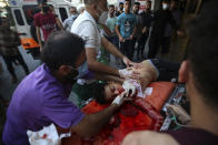 Medics and protestors move a wounded 13-year-old boy, who was shot by Israeli troops in his head during a protest at the Gaza Strip's border with Israel, into the treatment room of Shifa hospital in Gaza City, Saturday, Aug. 21, 2021. (AP Photo/Abdel Kareem Hana)