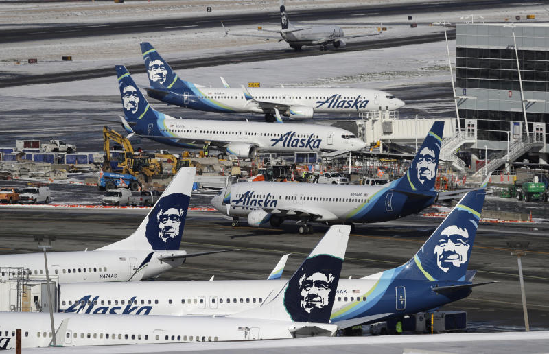 FILE - In this Feb. 5, 2019, file photo, Alaska Airlines planes are parked at a gate area at Seattle-Tacoma International Airport in Seattle. Alaska Airlines announced Monday, March 2, 2020, it will drop its sponsorship of the Iditarod, Alaska's most famous sporting event. The airline in a statement said the decision was made as it transitions to a new corporate giving strategy, but People for the Ethical Treatment of Animals, the most vocal critic of the thousand-mile sled dog race across Alaska, immediately took credit. (AP Photo/Ted S. Warren, File)