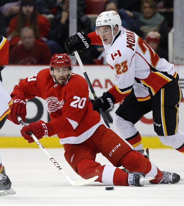 Detroit Red Wings' Drew Miller (20) tries to clear the puck away from Calgary Flames' Sean Monahan (23) during the second period of an NHL hockey game Thursday, Dec. 19, 2013, in Detroit. (AP Photo/Duane Burleson)