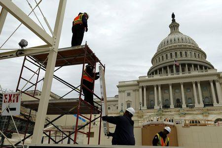 Workers construct the viewing stands ahead of Trump's inauguration at the U.S. Capitol in Washington