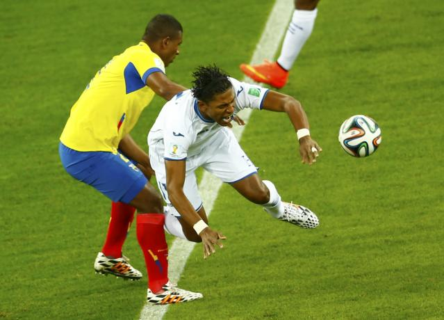 Ecuador's Jorge Guagua fights for the ball with Carlo Costly of Honduras (R) during their 2014 World Cup Group E soccer match at the Baixada arena in Curitiba June 20, 2014. REUTERS/Amr Abdallah Dalsh (BRAZIL - Tags: SOCCER SPORT WORLD CUP)