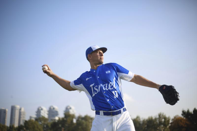 In this Tuesday, Jan. 14, 2020 photo, Danny Valencia throws a ball during Israel's national baseball team practice, in Tel Aviv, Israel. As a baseball-crazed kid growing up in Miami, Danny Valencia dreamed of playing in the Major Leagues. The thought of heading to the Olympics, for a foreign country no less, never crossed his mind. But that's the next surreal step for the 35-year-old Valencia, who recently became an Israeli citizen thanks to his Jewishness and is now the star player in Team Israel's improbable run to the Tokyo Games. (AP Photo/Ariel Schalit)