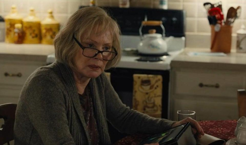 An elderly woman (Jean Smart) wearing glasses, sitting in a kitchen, and staring at something offscreen with a sullen look