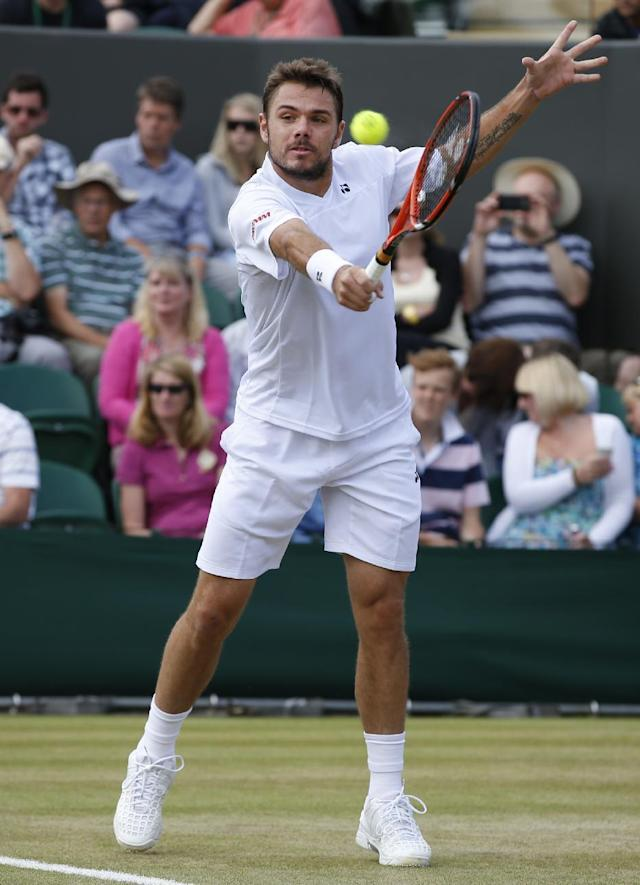 Stan Wawrinka of Switzerland plays a return to Denis Istomin of Uzbekistan during their men's singles match at the All England Lawn Tennis Championships in Wimbledon, London, Monday, June 30, 2014. (AP Photo/Alastair Grant)