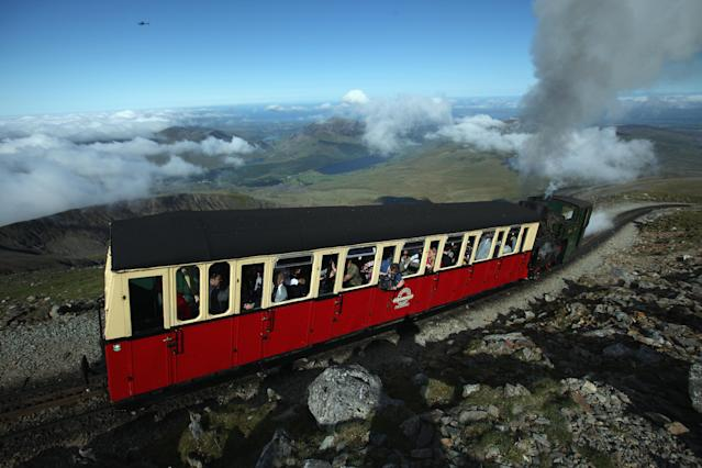 The Snowdon Mountain Railway carries Sir Chris Bonington and the Olympic torch to the summit of Mount Snowdon on May 29, 2012 in Llanberis, United Kingdom. Legendary mountaineer Sir Chris Bonington, aged 77, was given the honour of carrying the torch to the summit of Wales's highest mountain, the place his climbing career began 61 years ago. The Olympic Flame is now on day 11 of a 70-day relay involving 8,000 torchbearers covering 8,000 miles. (Photo by Christopher Furlong/Getty Images)