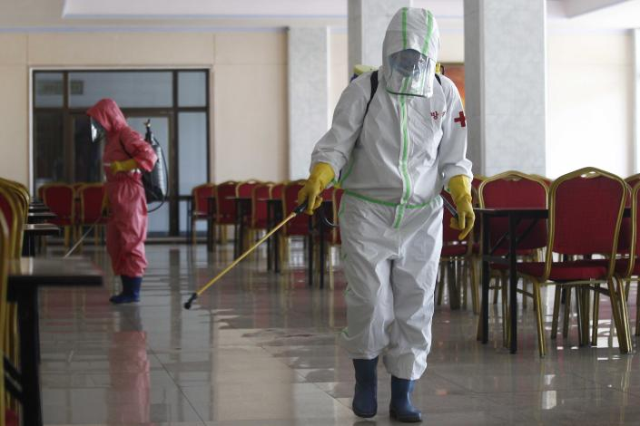 FILE - In this May 13, 2021, file photo, restaurant staff, in protective suit, disinfect the floor of Chongchun Restaurant in Pyongyang. After saying for months that it kept the coronavirus completely at bay, North Korea on Wednesday, June 30, came closest to admitting that its anti-virus campaign has been less than perfect. (AP Photo/Jon Chol Jin, File)