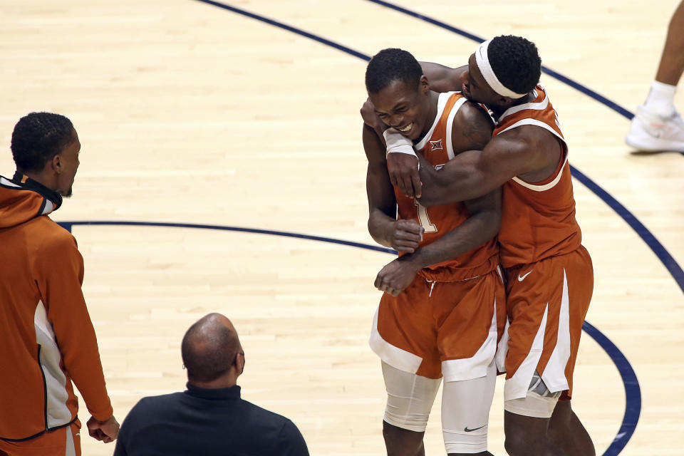 Texas guards Andrew Jones (1) and Courtney Ramey (3) celebrate after Jones scored against West Virginia during the second half of an NCAA college basketball game Saturday, Jan. 9, 2021, in Morgantown, W.Va. (AP Photo/Kathleen Batten)