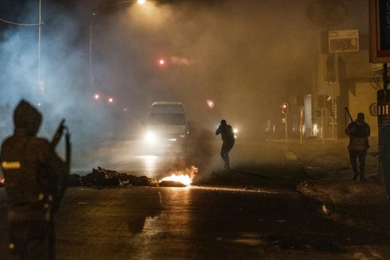 Night clashes: A police officer in the Johannesburg district of Jeppestown points his rifle at a minivan, forcing it to stop