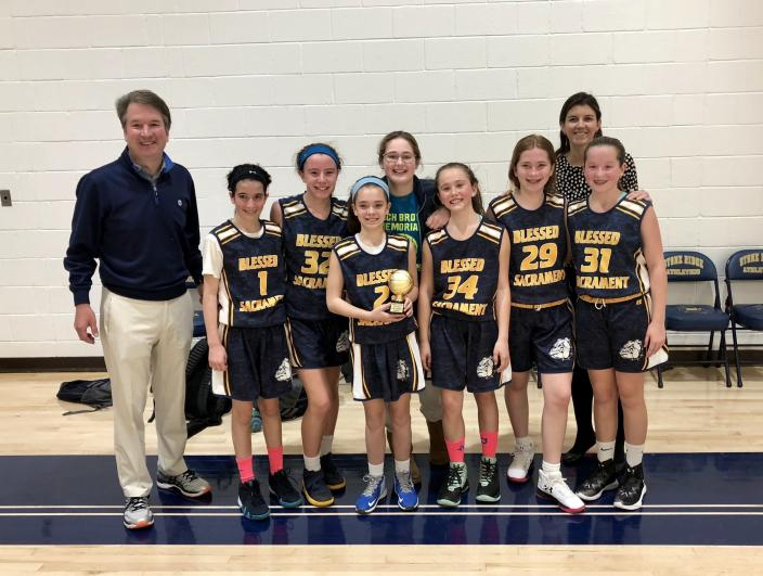 In this image provided by CRC Public Relations, Judge Brett Kavanaugh poses with his daughters basketball team which he coaches. Kavanaugh has been a conservative team player, and the Supreme Court nominee has stepped up to make a play at key moments in politics, government and the law dating to the Bill Clinton era. (CRC Public Relations via AP)