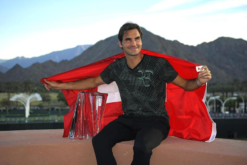 Roger Federer, of Switzerland, poses with his trophy and the Swiss flag after defeating Stan Wawrinka, also of Switzerland, in their final match at the BNP Paribas Open tennis tournament, Sunday, March 19, 2017, in Indian Wells, Calif. (AP Photo/Mark J. Terrill)