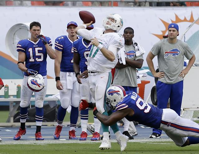 Miami Dolphins quarterback Ryan Tannehill attempts to throw a pass into the end zone as he is tackled by Buffalo Bills defensive end Mario Williams during the final seconds of an NFL football game, Sunday, Oct. 20, 2013, in Miami Gardens, Fla. The pass was incomplete and the Bills defeated the Dolphins 23-21. (AP Photo/Wilfredo Lee)