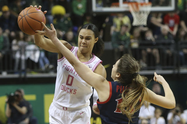 Oregon's Satou Sabally, left, and Arizona's Helena Pueyo reach for a loose ball during the third quarter of an NCAA college basketball game in Eugene, Ore., Friday, Feb. 7, 2020. (AP Photo/Chris Pietsch)