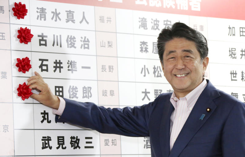 Japanese Prime Minister Shinzo Abe smiles in front of red rosettes on the names of his Liberal Democratic Party's winning candidates during ballot counting for the upper house elections at the party headquarters in Tokyo, Sunday, July 21, 2019. Prime Minister Abe's ruling coalition appeared certain to hold onto a majority in Japan's upper house of parliament, with exit polls from Sunday's election indicating he could even close in on the super-majority needed to propose constitutional revisions.(AP Photo/Koji Sasahara)