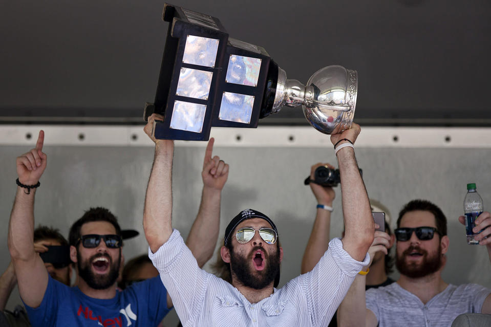 FILE - In this June 13, 2012, file photo, Norfolk Admirals captain Mike Angelidis lifts the Calder Cup over his head at Scope Plaza after the conclusion of the parade through downtown Norfolk, Va. Jon Cooper is one victory by his Tampa Bay Lightning away from becoming just the second coach in the NHL's salary-cap era to win the Stanley Cup in back-to-back seasons. Cooper also won the American Hockey League's Calder Cup in 2012 with Norfolk after going on a 28-game winning streak during the season. (Sean Proctor/The Virginian-Pilot via AP, File)