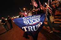 A supporter of President Trump waves a flag in front of the Clark County Election Department, Thursday, Nov. 5, 2020, in Las Vegas. (AP Photo/Jae C. Hong)