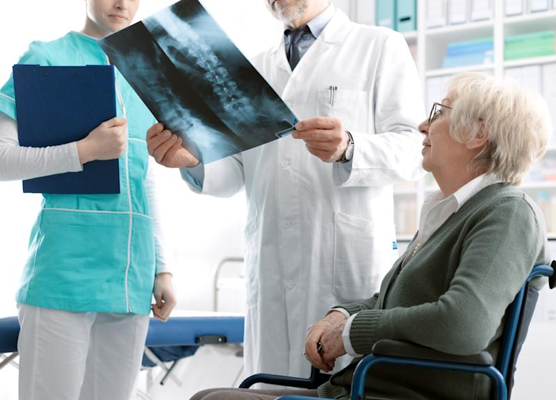 Doctor checking a senior female patient's x-ray image during a visit at the hospital, injury and osteoporosis concept