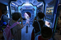 Visitors take smartphone photos of a child posing at a mock space station at an exhibition promoting China's achievements under the Communist Party from 1921 to 2021, in Beijing, Tuesday, June 22, 2021. Authorities in the capital city are gearing up to mark the 100th anniversary of the founding of China's ruling Communist Party, which will be observed on July 1. (AP Photo/Andy Wong)