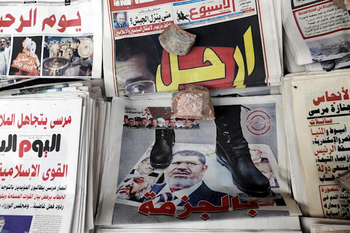 "Front pages of Egyptian independent newspapers are fronted by his pictures with Arabic title read, "" leave,"" and "" by shoe"" in Tahrir Square in Cairo, Egypt, Wednesday, July 3, 2013. Egypt's military held an emergency meeting Wednesday hours ahead of its deadline for the country's embattled Islamist president to yield to the demands of millions of protesters or face intervention by the army, a defense official said.(AP Photo/Amr Nabil)"