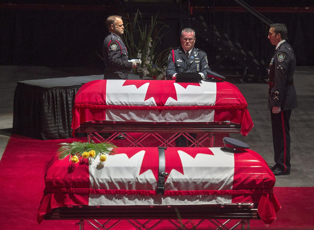 <p>Members of the Fredericton Police Force place medals, hat and ceremonial belt on the casket for Const. Robb Costello at the regimental funeral for Costello and Const. Sara Burns, killed in the line of duty, in Fredericton on Saturday, Aug. 18, 2018. The two city police officers were among four people who died in a shooting in a residential area on the city's north side. (Photo from The Canadian Press/Andrew Vaughan) </p>