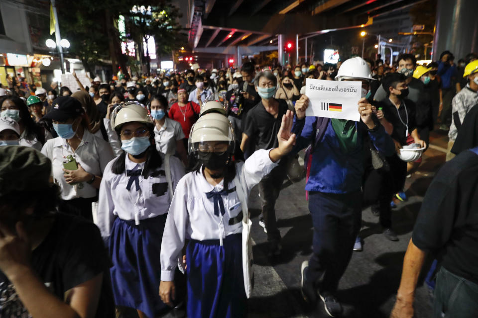 """Pro-democracy protesters flashing three fingers as they march to the German Embassy in central Bangkok, Thailand, Monday, Oct. 26, 2020. As lawmakers debated in a special session in Parliament that was called to address political tensions, student-led rallies were set to continue with a march through central Bangkok on Monday evening to the German Embassy, apparently to bring attention to the time King Maha Vajiralongkorn spends in Germany. The sign translated reads, """"People see you in Germany."""" (AP Photo/Gemunu Amarasinghe)"""