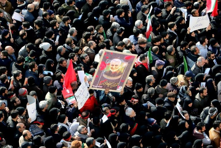 Iranian mourners carry a picture of military commander Qasem Soleimani, killed in a US drone strike in Baghdad, during a funeral procession in Tehran in January, 2020