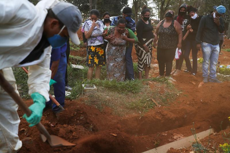 Relatives react during the burial of 64-year-old Raimunda Conceicao Souza at Vila Formosa cemetery, Brazil's biggest cemetery: REUTERS