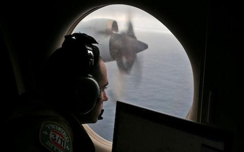 Rayan Gharazeddine scans the water in the southern Indian Ocean off Australia from a Royal Australian Air Force AP-3C Orion during a search for the missing plane in 2014 - Credit: Rob Griffith/AP