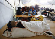 A child rests as other migrants wait inside a tent at the the Berlin Office of Health and Social Affairs (LAGESO), in Berlin, Germany, January 5, 2016. REUTERS/Hannibal Hanschke