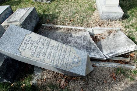 A headstone, pushed off its base by vandals, lays on the ground near a smashed tomb in the Mount Carmel Cemetery, a Jewish cemetery, in Philadelphia, Pennsylvania, U.S. February 27, 2017. REUTERS/Tom Mihalek