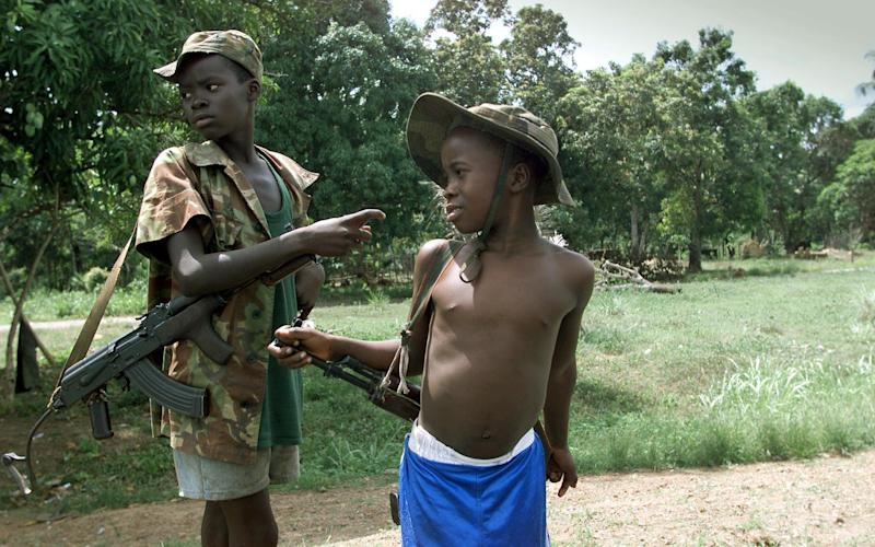 Two children enrolled with Sierra Leonean troops fighting rebels of the Revolutionary United Front getting ready to fight on the frontline in March 2000 - Credit: AFP/Getty Images