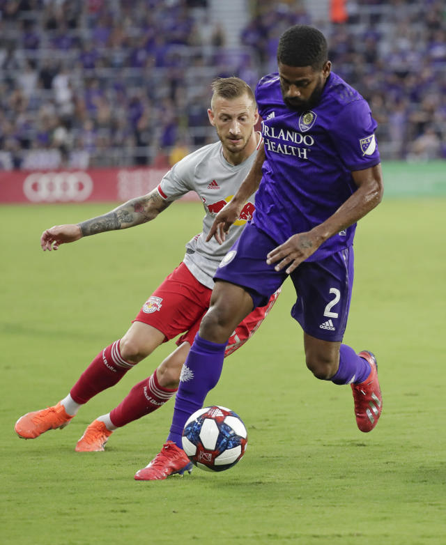 Orlando City's Ruan (2) pushes the ball away from New York Red Bulls' Daniel Royer, left, during the first half of an MLS soccer match, Sunday, July 21, 2019, in Orlando, Fla. (AP Photo/John Raoux)