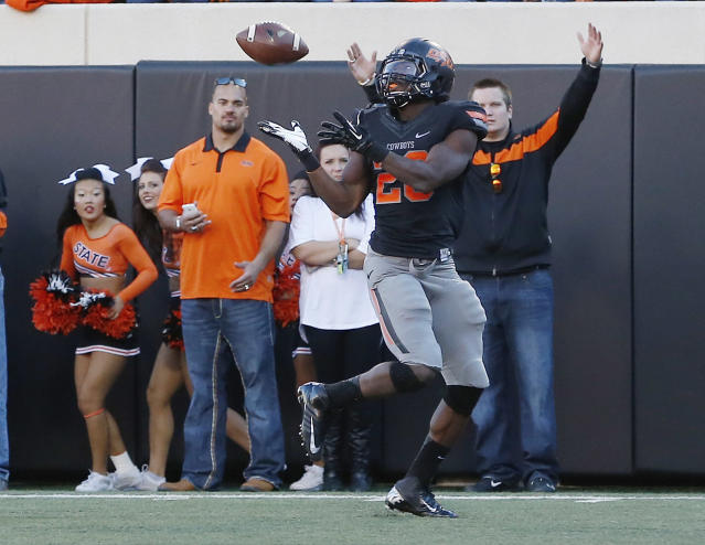 CORRECTS TO DESMOND ROLAND, INSTEAD OF TRACY MOORE - Oklahoma State's Desmond Roland catches a pass for a touchdown against Kansas in the second quarter of an NCAA college football game in Stillwater, Okla., Saturday, Nov. 9, 2013. (AP Photo/Sue Ogrocki)