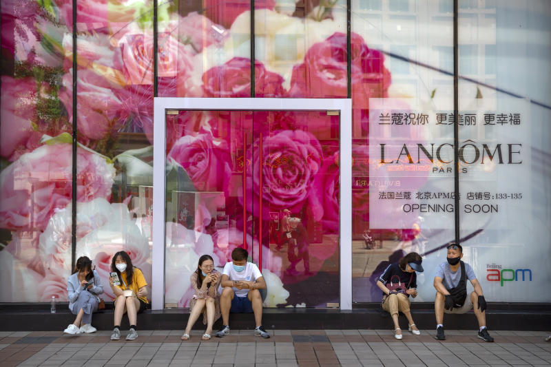 People wearing face masks to protect against the new coronavirus sit in front of a Lancome cosmetics store under construction at a pedestrian shopping street in Beijing, Saturday, June 6, 2020. China's capital is lowering its emergency response level to the second-lowest starting Saturday for the coronavirus pandemic. That will lift most restrictions on people traveling to Beijing from Wuhan and surrounding Hubei province, where the virus first appeared late last year. (AP Photo/Mark Schiefelbein)