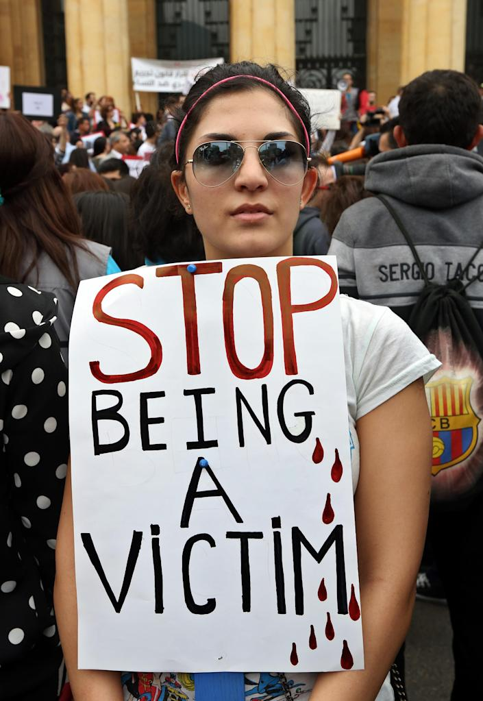 A Lebanese woman holds a placard to mark International Woman's Day during a rally by thousands demanding that parliament approves a law that protects women from domestic violence in Beirut, Lebanon, Saturday, March. 8, 2014. Although Lebanon appears very progressive on women rights compared to other countries in the Middle East, domestic violence remains an unspoken problem and the nation's parliament has yet to vote on a bill protecting women's rights nearly three years after it was approved by the Cabinet. (AP Photo/Bilal Hussein)